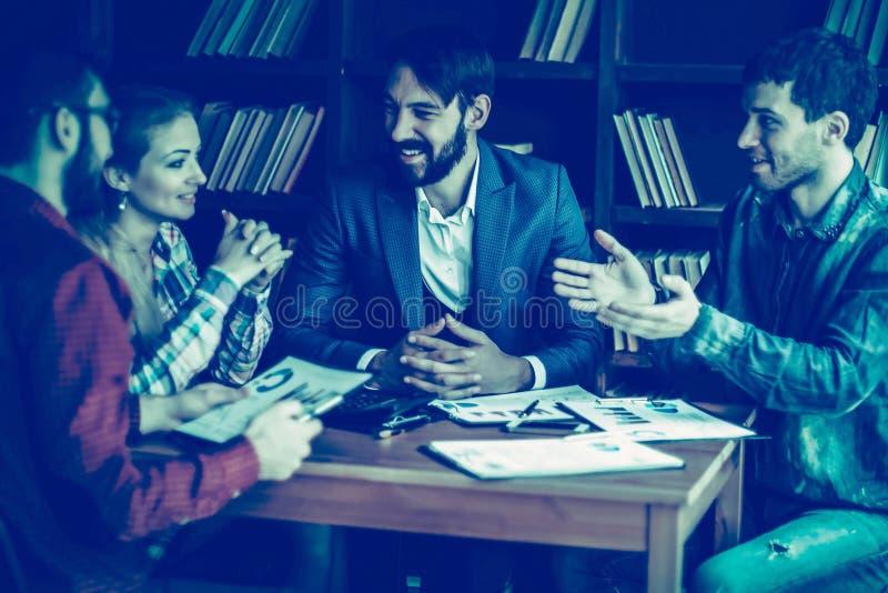 Equipo del negocio que discute un informe financiero sobre el ` s de la compa??a favorable fotos de archivo