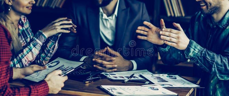 Equipo del negocio que discute un informe financiero sobre el ` s de la compa??a favorable imágenes de archivo libres de regalías