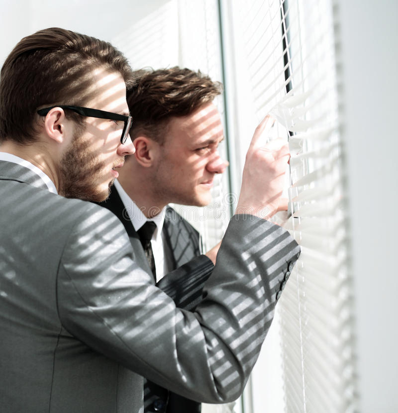 Equipo del negocio que empuja las persianas y que mira hacia fuera el viento de la oficina fotografía de archivo libre de regalías