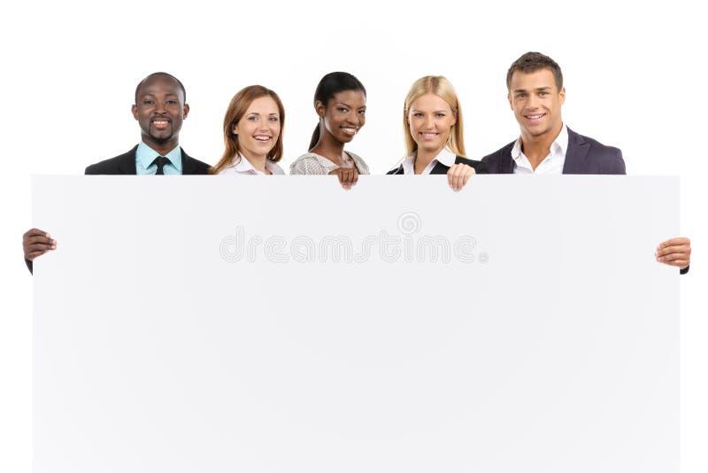 Equipo del negocio que lleva a cabo al tablero blanco imagenes de archivo