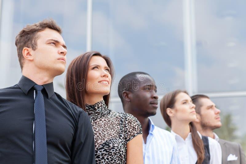 Equipo del negocio que se coloca en fila en la oficina y que mira hacia arriba - al equipo acertado del negocio fotos de archivo