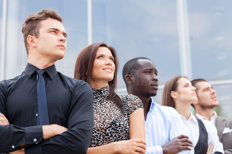 Equipo del negocio que se coloca en fila en la oficina y que mira hacia arriba - al equipo acertado del negocio fotografía de archivo libre de regalías