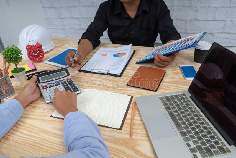Equipo del negocio que se sienta alrededor de la tabla y que trabaja con el informe de papel de la carta socios acertados que dis fotografía de archivo libre de regalías