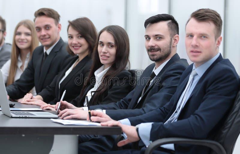 Download Equipo Del Negocio Que Se Sienta En El Escritorio En La Sala De Conferencias Foto de archivo - Imagen de trabajo, confidente: 100535200