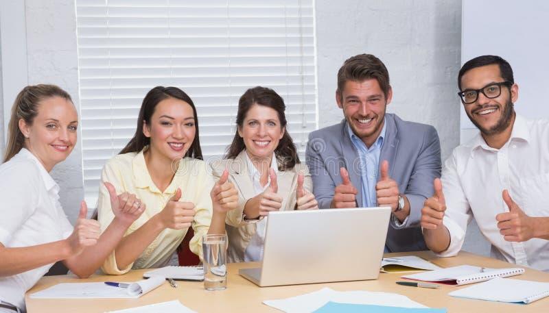Equipo del negocio que sonríe en la cámara que muestra los pulgares para arriba foto de archivo libre de regalías