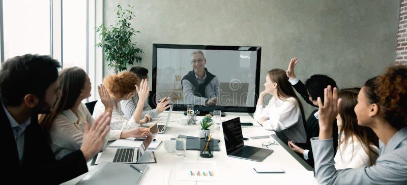 Equipo del negocio que tiene llamada video con el jefe mayor en la oficina fotos de archivo libres de regalías
