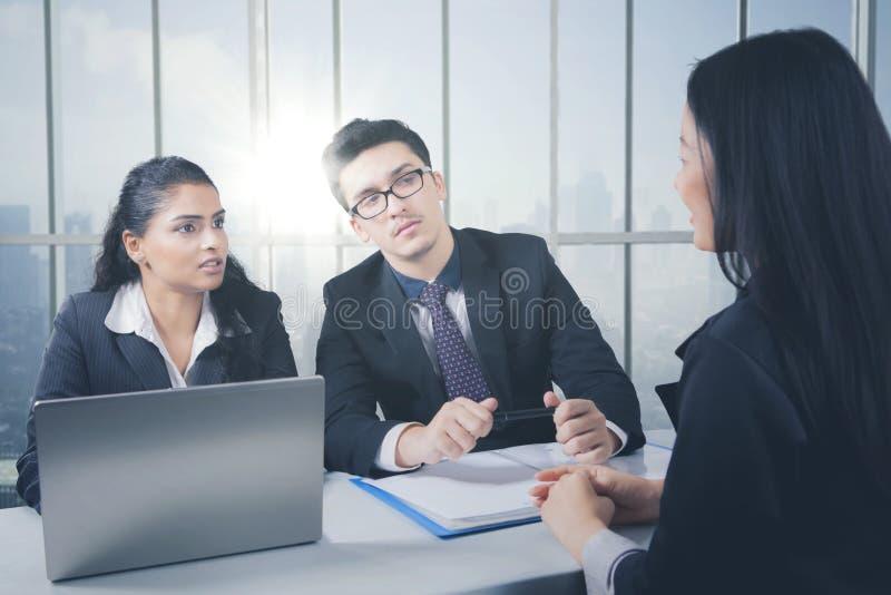 Equipo del negocio que tiene una discusión mientras que trabaja en el ordenador portátil fotografía de archivo