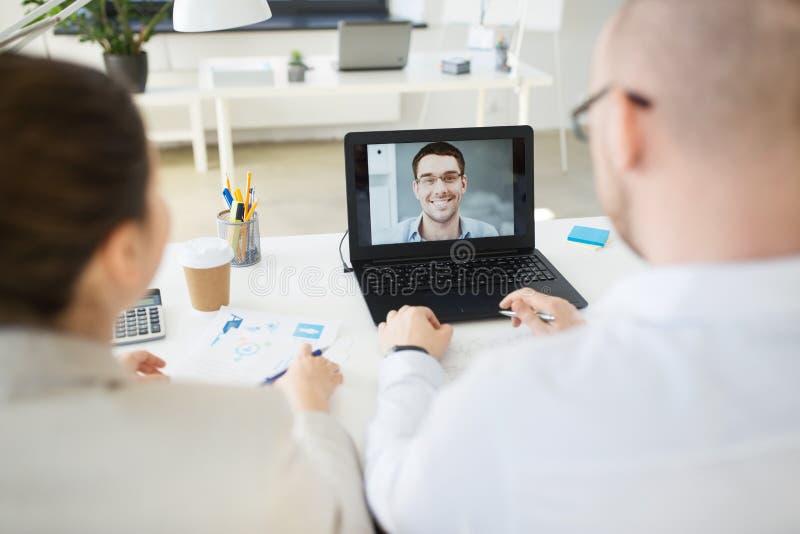 Equipo del negocio que tiene videoconferencia en la oficina foto de archivo