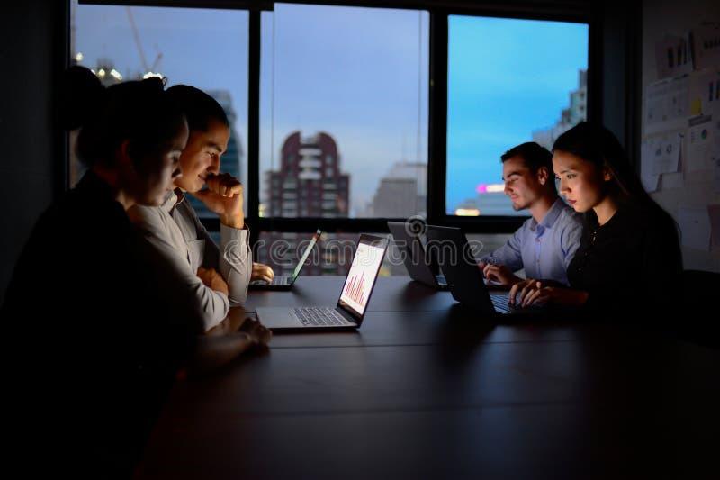 Equipo del negocio que trabaja con el ordenador en horas extras en la noche imagen de archivo libre de regalías