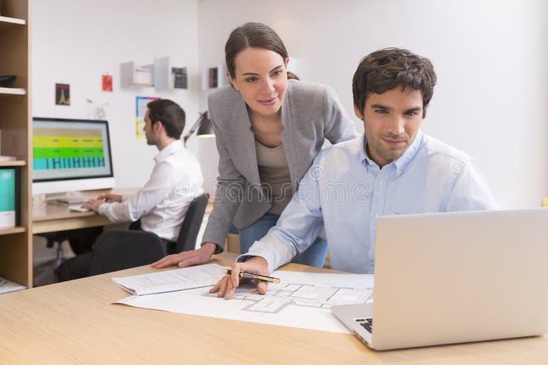 Equipo del negocio que trabaja en el ordenador portátil en oficina imagen de archivo libre de regalías