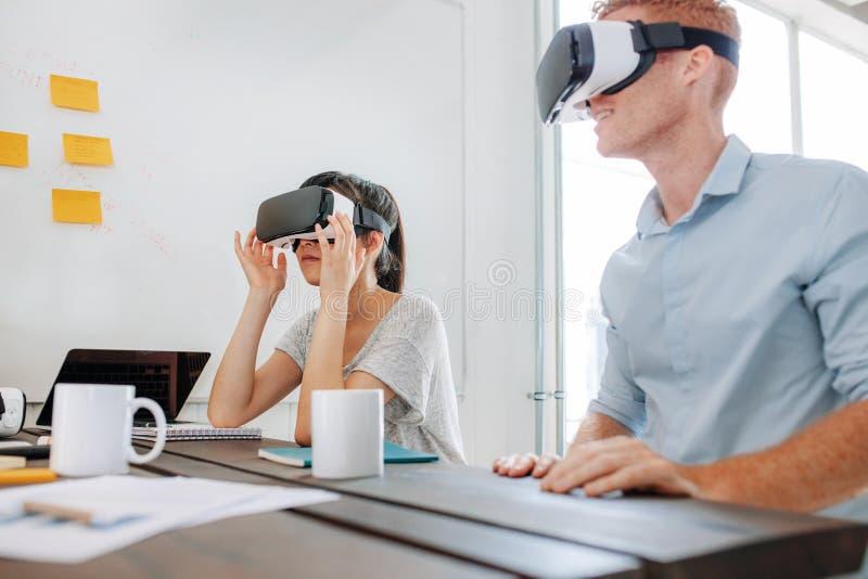 Equipo del negocio usando las auriculares de la realidad virtual en la reunión imagen de archivo