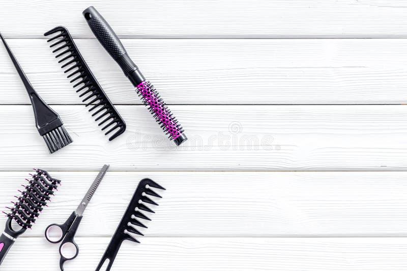 Equipo del peluquero para cortar el pelo y diseñarlo con los peines, sciccors en el copyspace de madera blanco de la opinión de t fotos de archivo
