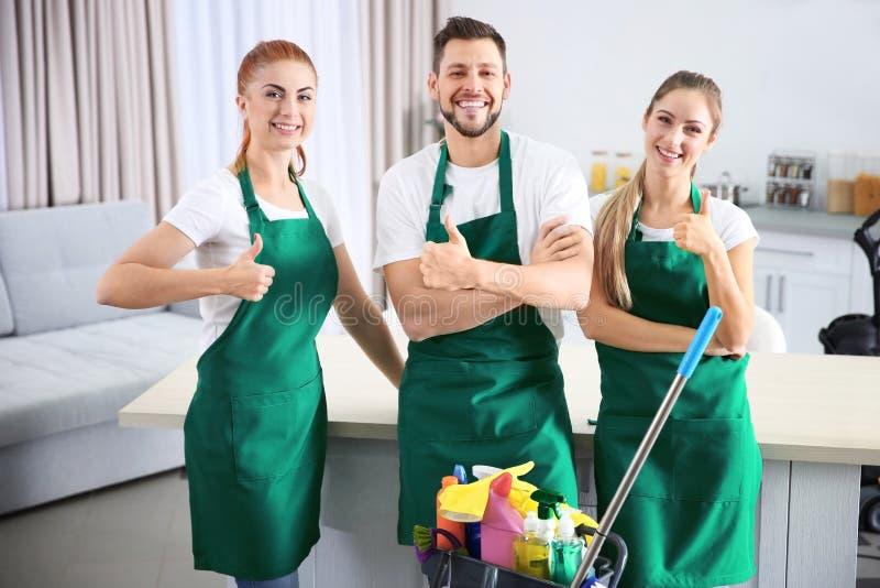 Equipo del servicio de la limpieza en el trabajo en cocina foto de archivo