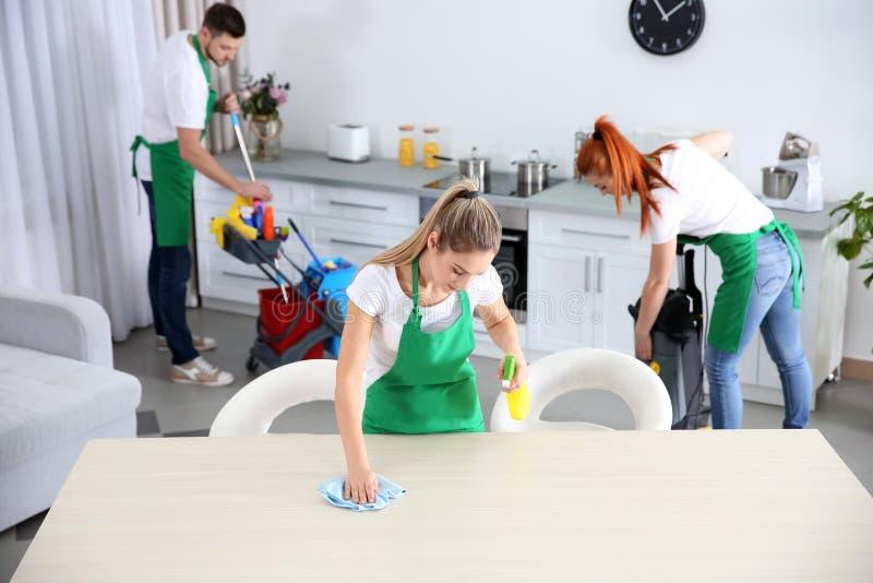Equipo del servicio de la limpieza que trabaja en cocina foto de archivo