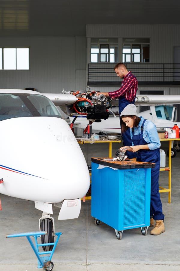 Equipo del servicio de los aviones que repara a Jet Plane fotos de archivo libres de regalías