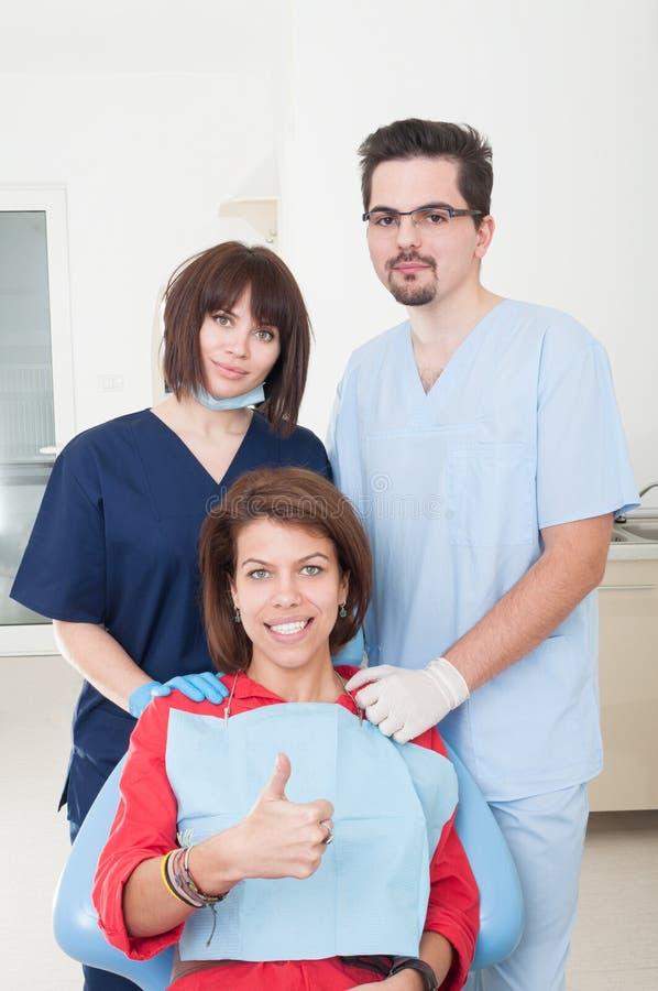 Equipo dental que toma cuidado del paciente femenino foto de archivo libre de regalías