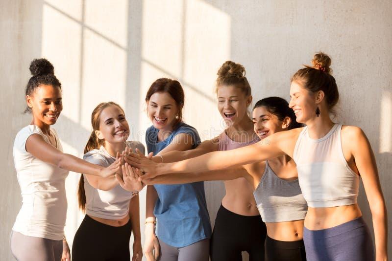 Equipo deportivo de la muchacha que comienza entrenamiento a poner sus manos juntas imagen de archivo