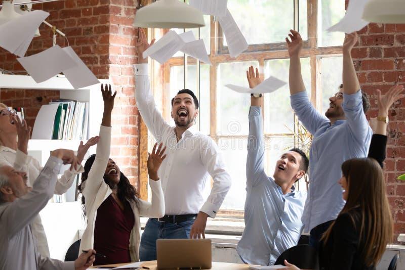 Equipo diverso eufórico del negocio que lanza los papeles que lanzan para celebrar la victoria del éxito foto de archivo libre de regalías