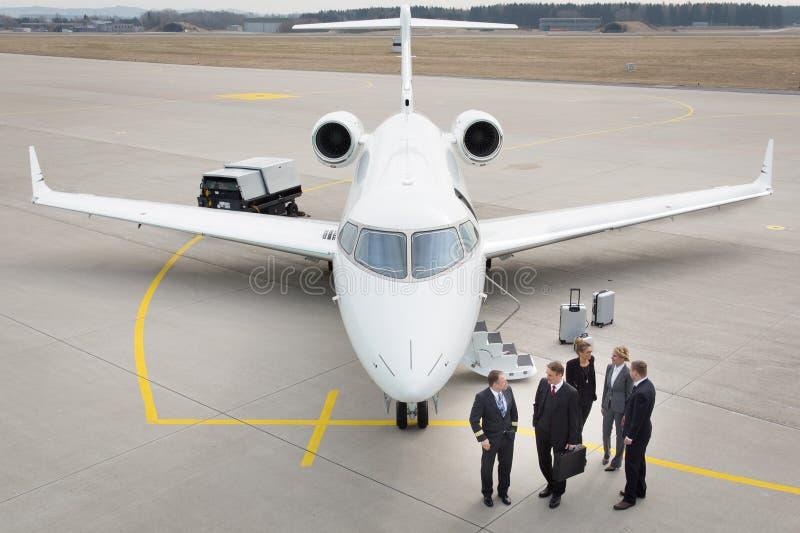 Equipo ejecutivo del negocio delante del jet corporativo que habla con el pil imágenes de archivo libres de regalías