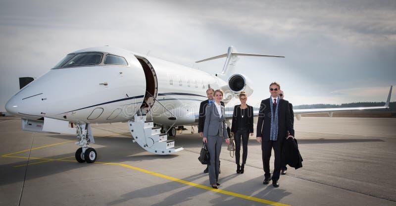 Equipo ejecutivo del negocio que deja el jet corporativo imagenes de archivo