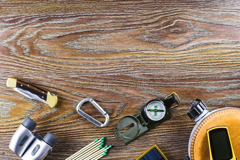 Equipo el caminar o del viaje con el compás, prismáticos, partidos en fondo de madera Concepto activo de la forma de vida imágenes de archivo libres de regalías