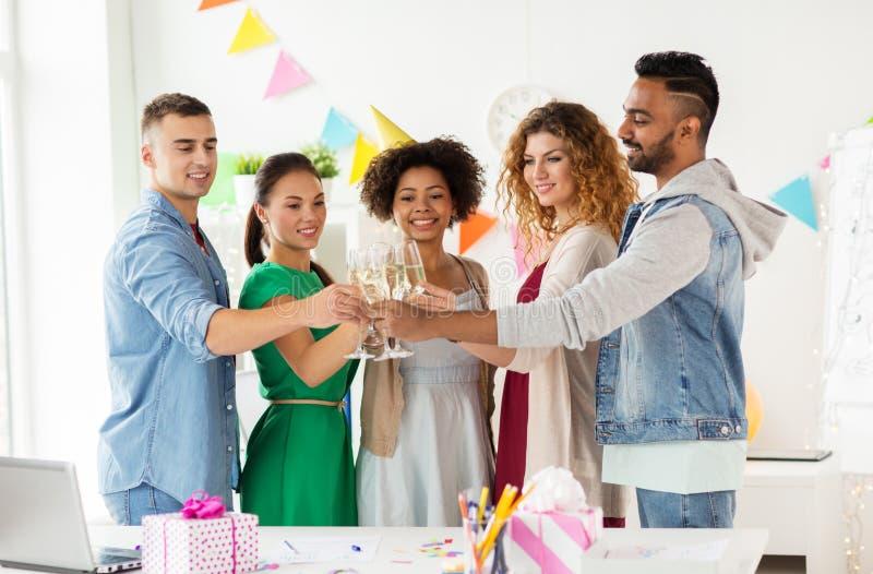 Equipo feliz con champán en la fiesta de cumpleaños de la oficina imagenes de archivo