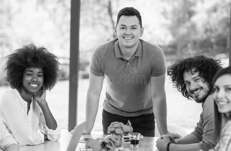 Equipo feliz de los jóvenes que sonríe en el trabajo fotos de archivo