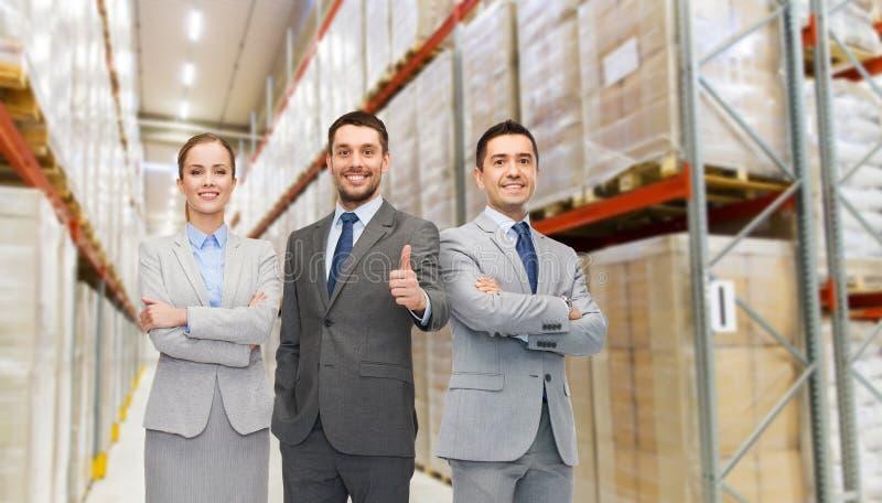Equipo feliz del negocio en el almacén que muestra los pulgares para arriba fotos de archivo