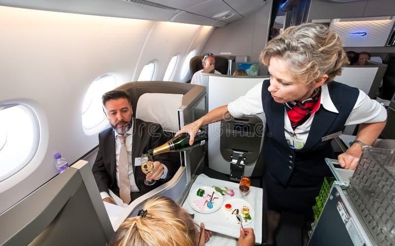 Equipo femenino de la cabina que vierte un vidrio de chamán en clase de negocios de un Airbus A380 imagenes de archivo