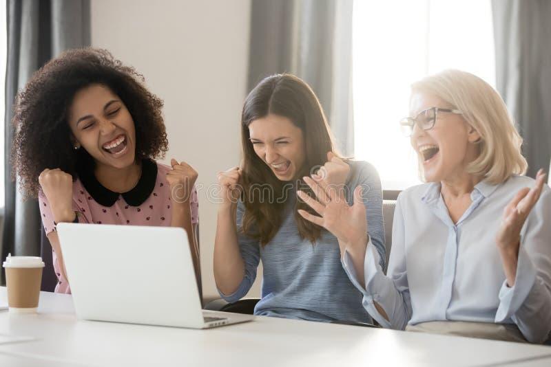Equipo femenino extático feliz diverso de los empleados emocionado por triunfo en línea imagen de archivo libre de regalías