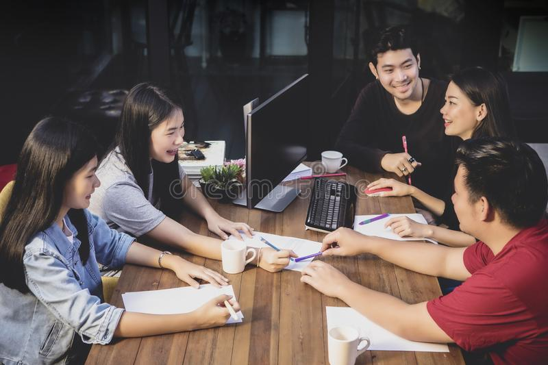 Equipo independiente asiático que acepilla para el trabajo en equipo en sala de reunión de la oficina foto de archivo libre de regalías