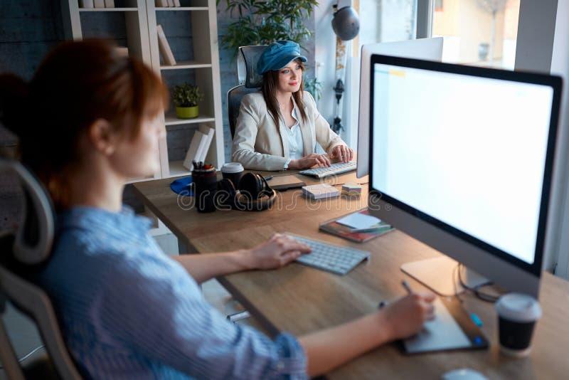Equipo independiente del diseñador que trabaja tarde en el ordenador imagenes de archivo