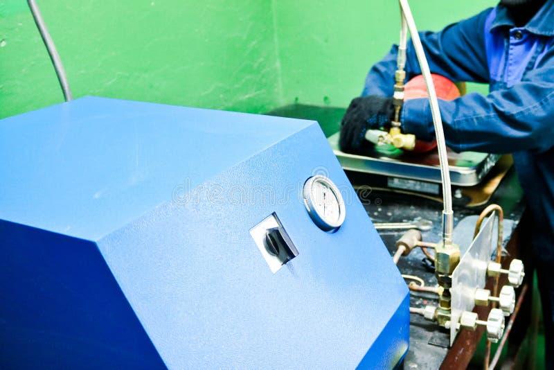 Equipo industrial profesional, estación para los extintores de carga con los indicadores de presión y mangueras en el taller imagen de archivo