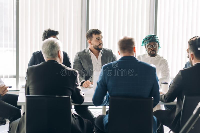 Equipo interracial corporativo del negocio con el líder alegre en una reunión, cierre para arriba imagen de archivo