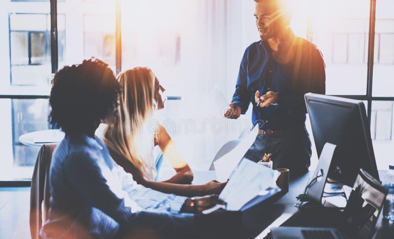 Equipo joven de compañeros de trabajo que hacen la gran discusión de la reunión en oficina coworking moderna Hombre de negocios h foto de archivo