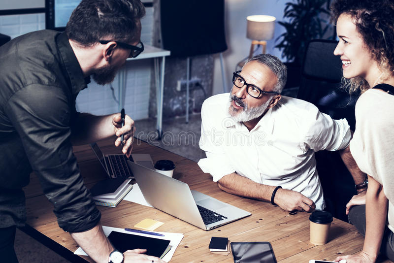 Equipo joven de compañeros de trabajo que hacen la gran discusión del trabajo en oficina moderna Hombre barbudo que habla con el  fotos de archivo libres de regalías