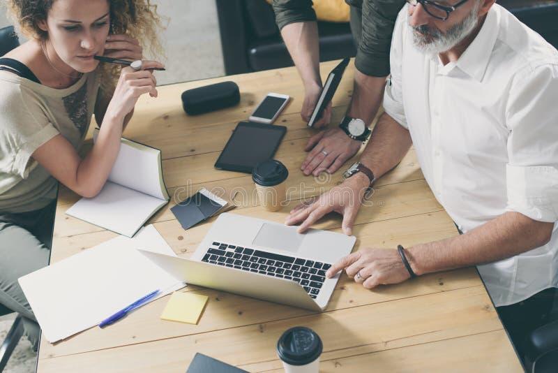 Equipo joven de compañeros de trabajo que hacen la gran discusión del trabajo en oficina moderna Hombres de negocios que hacen fr foto de archivo libre de regalías