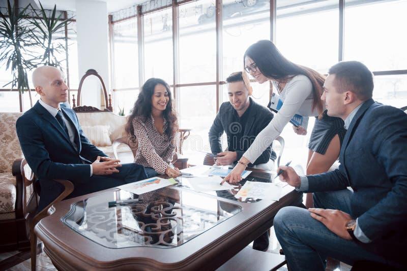 Equipo joven de compañeros de trabajo que hacen la gran discusión del negocio en oficina coworking moderna Concepto de la gente d imagen de archivo