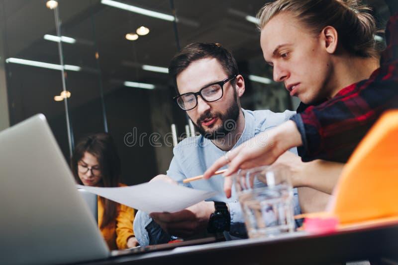 Equipo joven de compañeros de trabajo que hacen nuevo proyecto en oficina grande moderna del desván El planeamiento de trabajo de foto de archivo