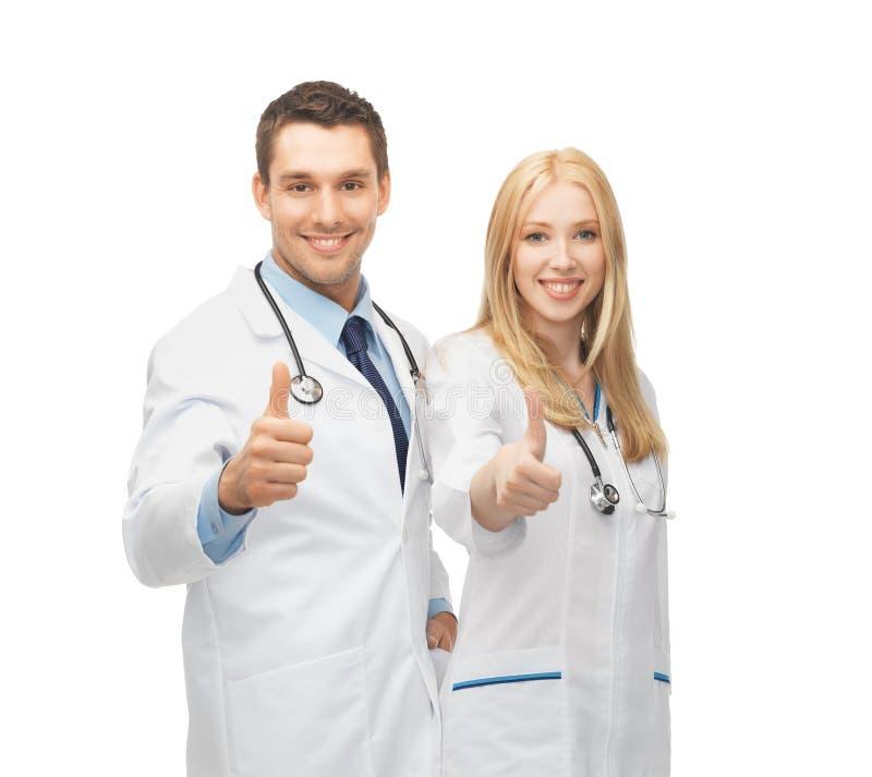 Equipo joven de dos doctores que muestran los pulgares para arriba foto de archivo
