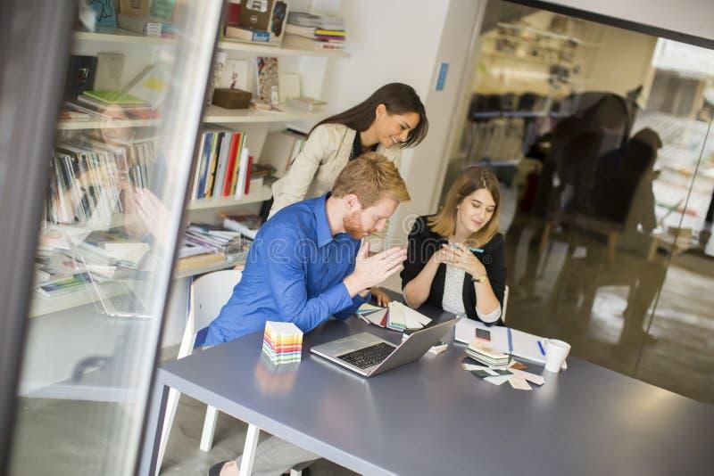 Equipo joven del negocio que trabaja en una oficina moderna imagenes de archivo