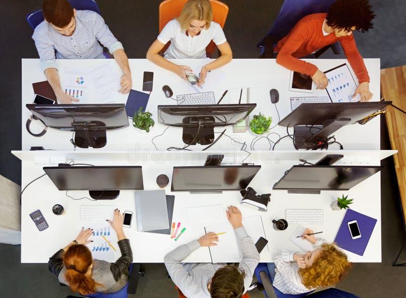 Equipo joven diverso que trabaja en el lugar coworking, visión superior foto de archivo