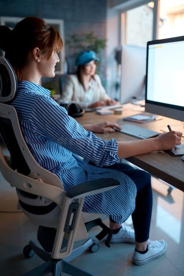 Equipo joven que trabaja en la oficina - diseñadores de sexo femenino que trabajan en horas extras imágenes de archivo libres de regalías