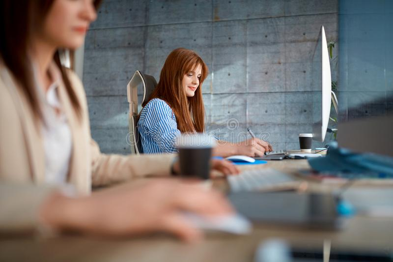 Equipo joven que trabaja en la oficina - trabajo femenino de los diseñadores imagen de archivo