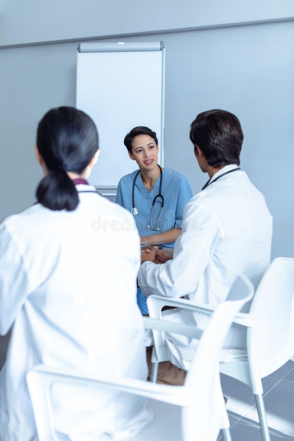 Equipo médico diverso que se sienta y que discute en la tabla imagenes de archivo