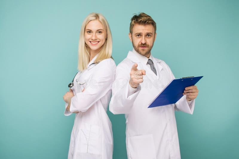 Equipo médico feliz de doctores, de hombre que señala a la cámara y de mujer sonriente foto de archivo