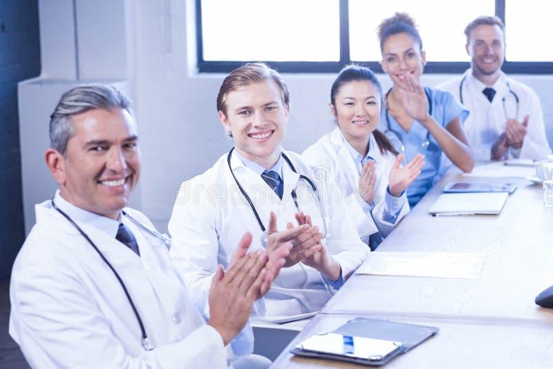 Equipo médico que aplaude en la reunión imagen de archivo