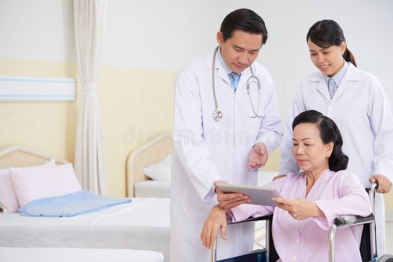 Equipo médico que habla con el paciente fotografía de archivo libre de regalías