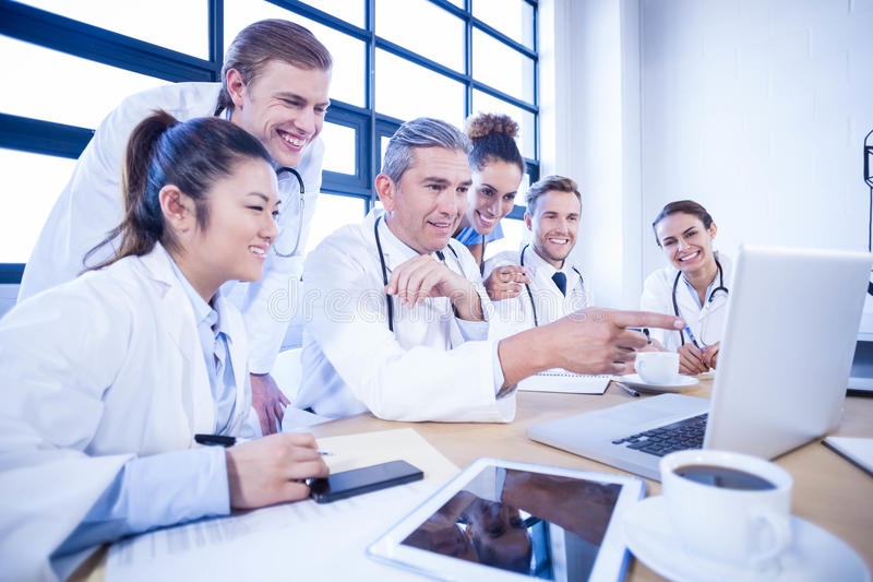 Equipo médico que mira en el ordenador portátil y que tiene una discusión fotografía de archivo