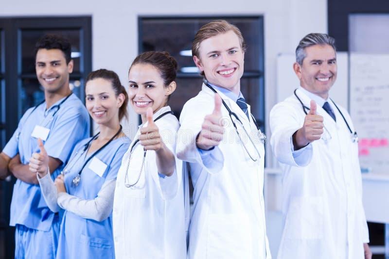 Equipo médico que pone sus pulgares y la sonrisa imagen de archivo